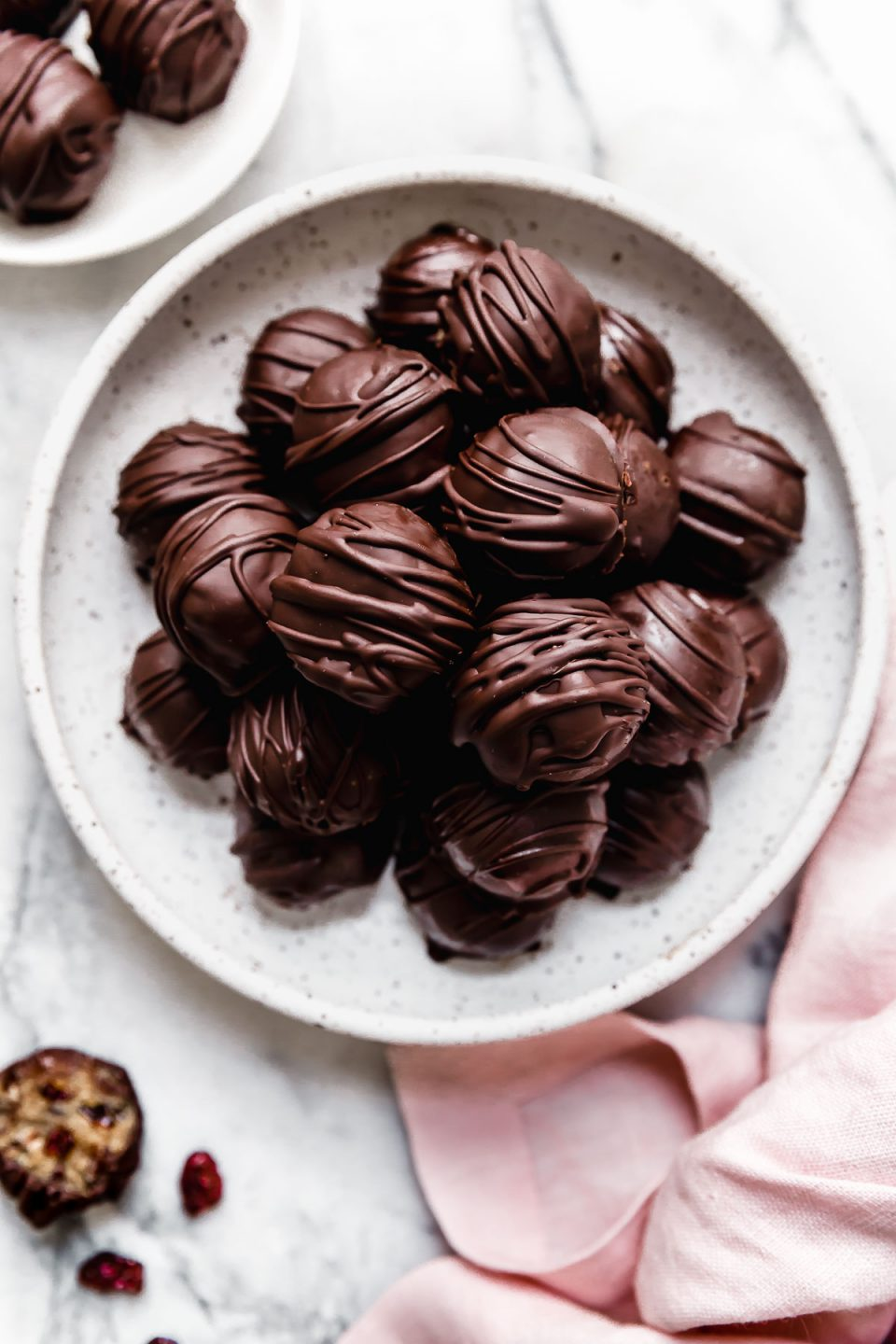 Chocolate-covered vegan cookie dough bites in a white serving bowl.