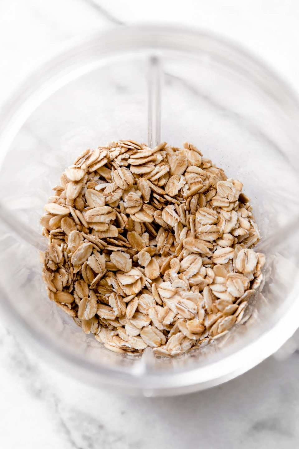 Rolled oats in a blender cup for making oat flour.