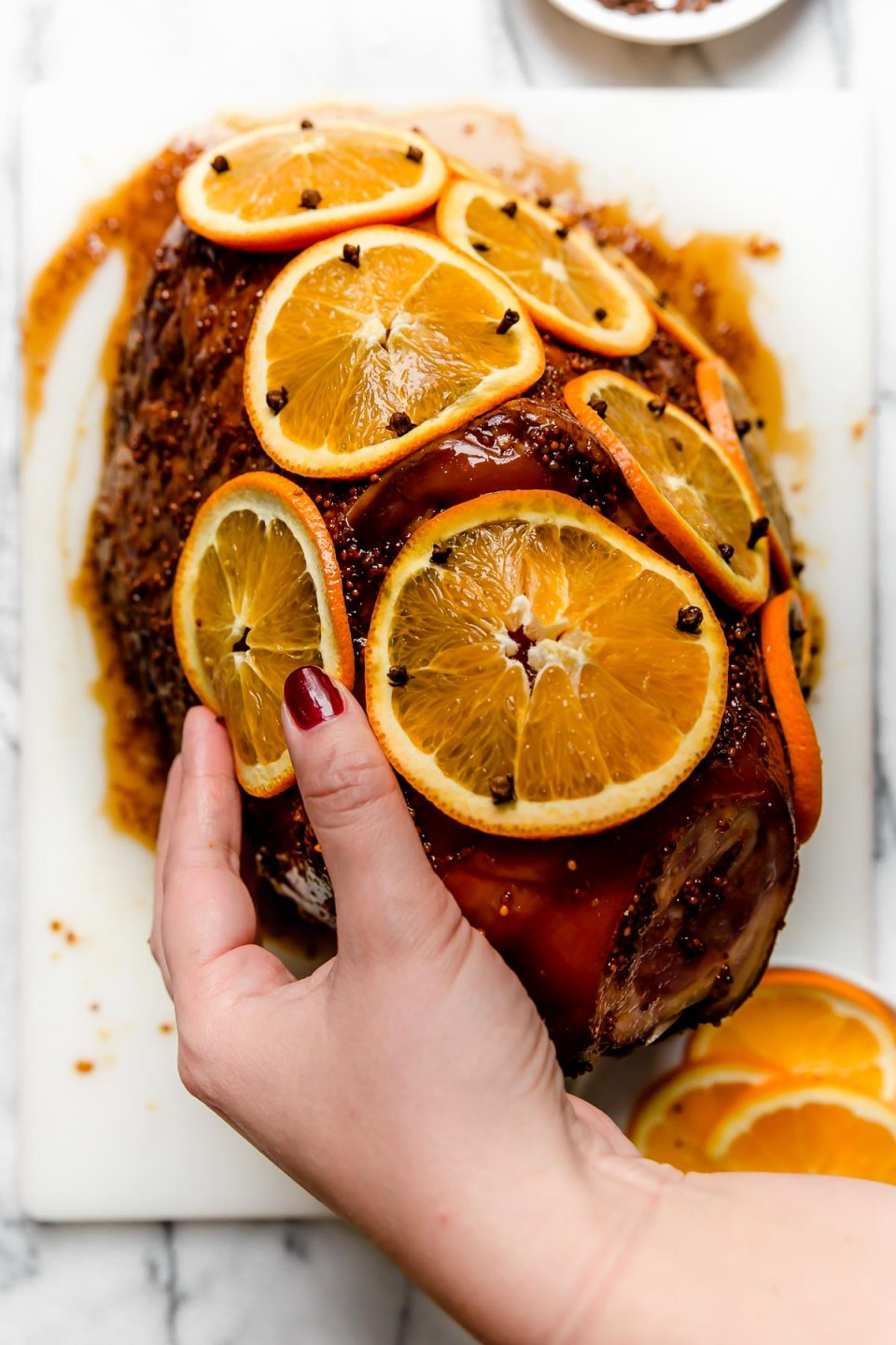 Woman's hands shown studding thinly sliced oranges on ham with whole cloves.