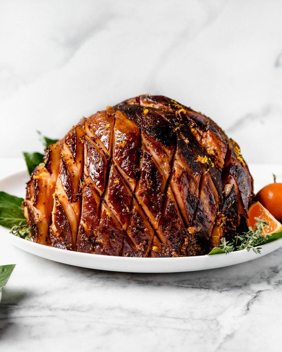 Citrus & Maple Glazed ham on a white serving platter, with fresh bay leaves, fresh rosemary, fresh thyme, & oranges.