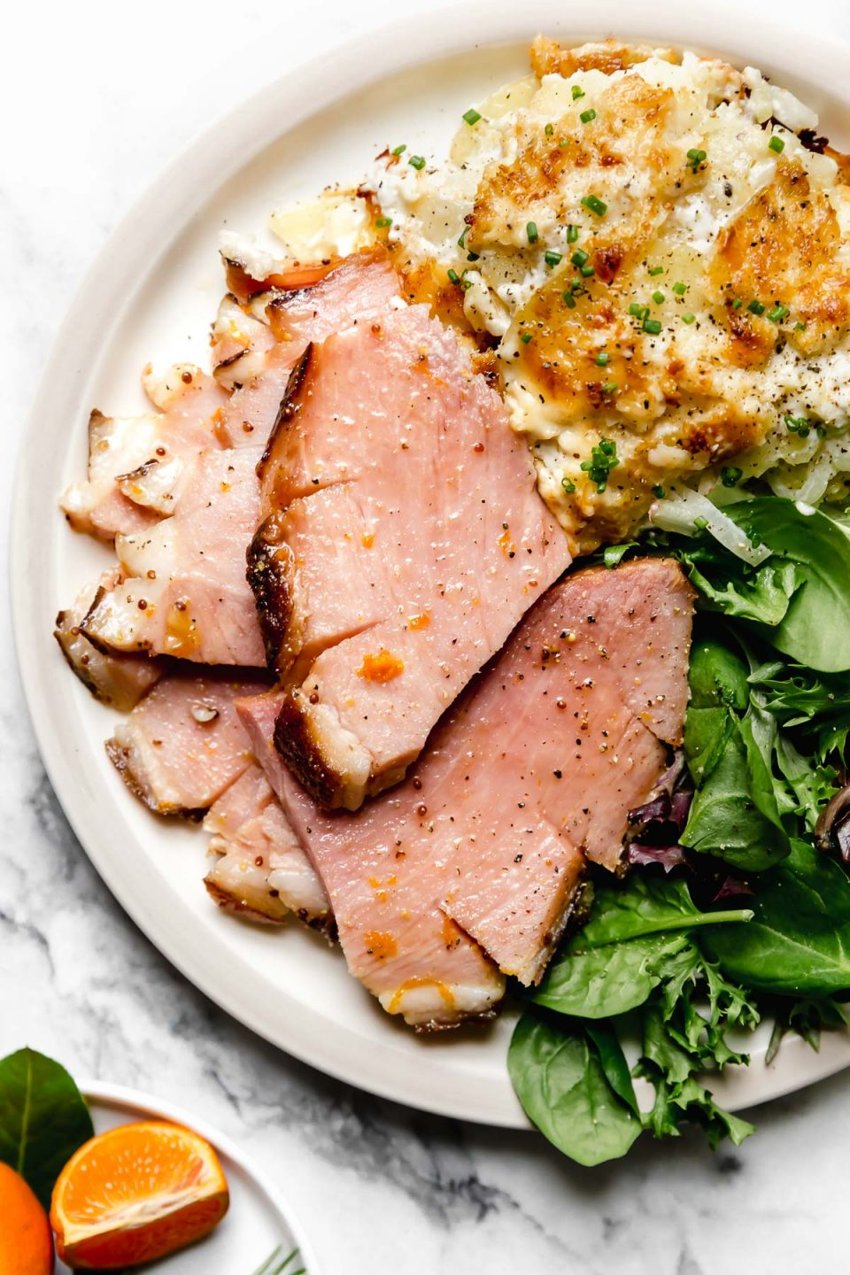 Thick slices maple glazed baked ham, plated on a dinner plate with greens & au gratin potatoes.