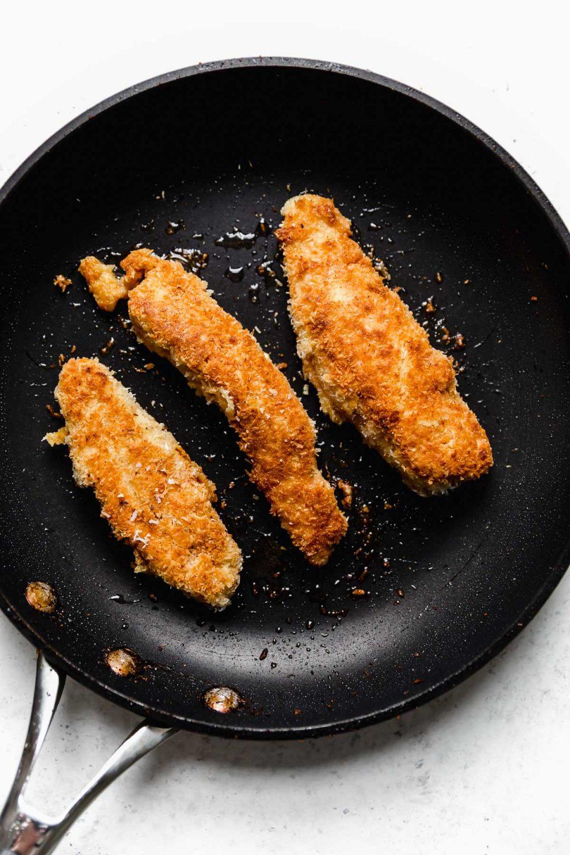 Pan-frying coconut chicken tenders in a black skillet.