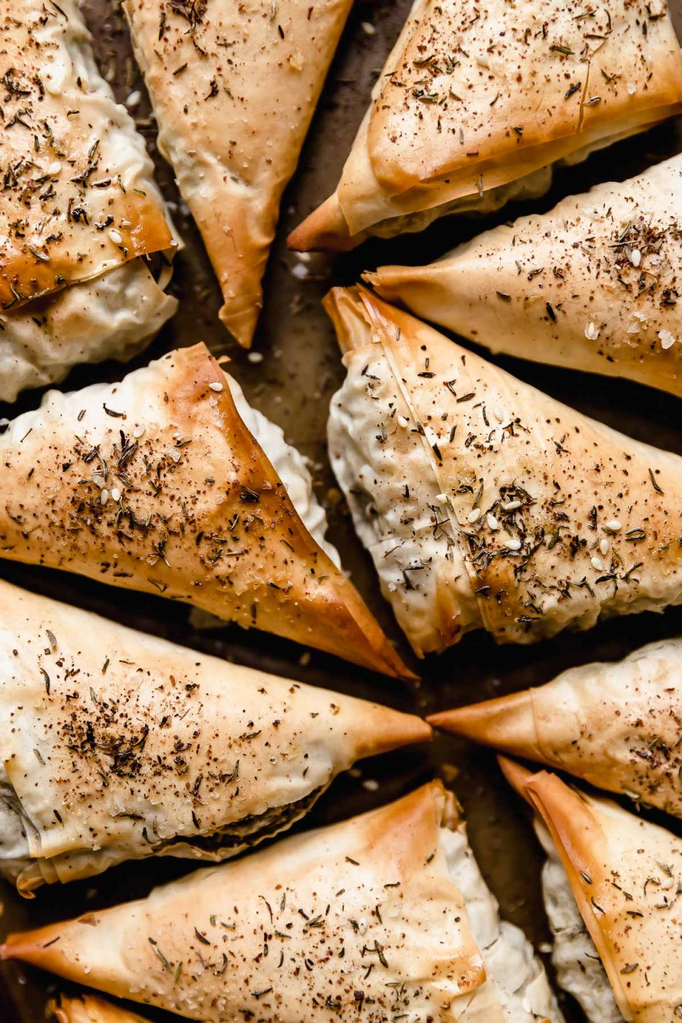 Baked spanakopita triangles on a baking sheet.