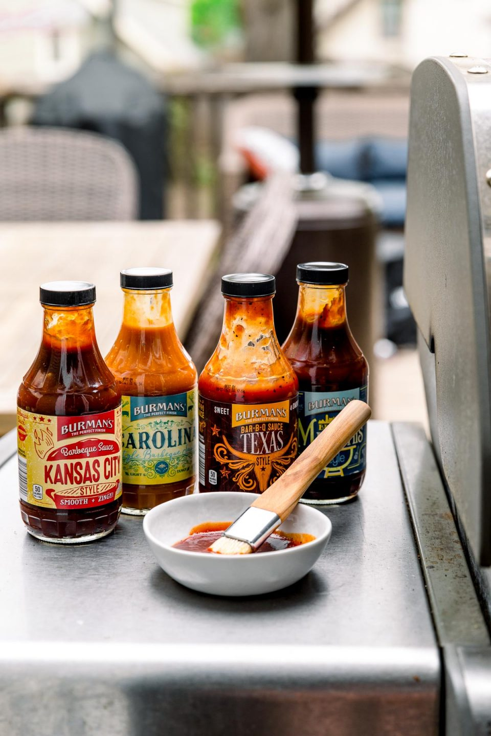 4 bottles of BBQ sauce sitting next to a Weber grill. One sauce has been poured into a small white bowl, with a small pastry brush for basting.