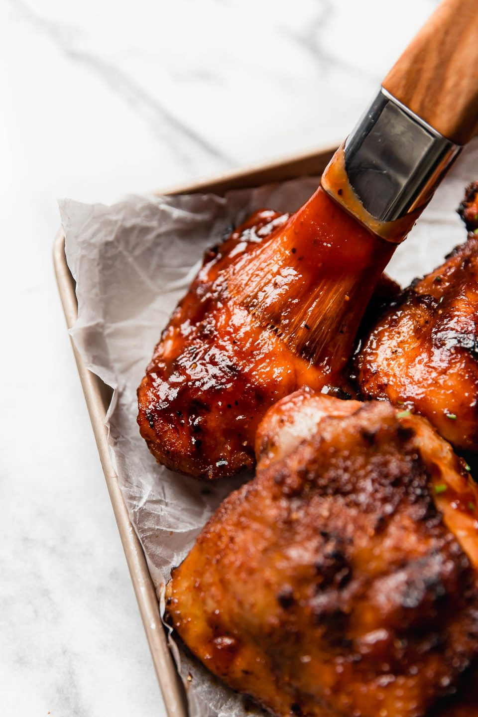 Grilled barbecue chicken thighs getting brushed with BBQ sauce.