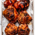 6 grilled BBQ chicken thighs on a small baking sheet. Some of the chicken pieces are slathered in barbecue sauce, while others have crispy skin.