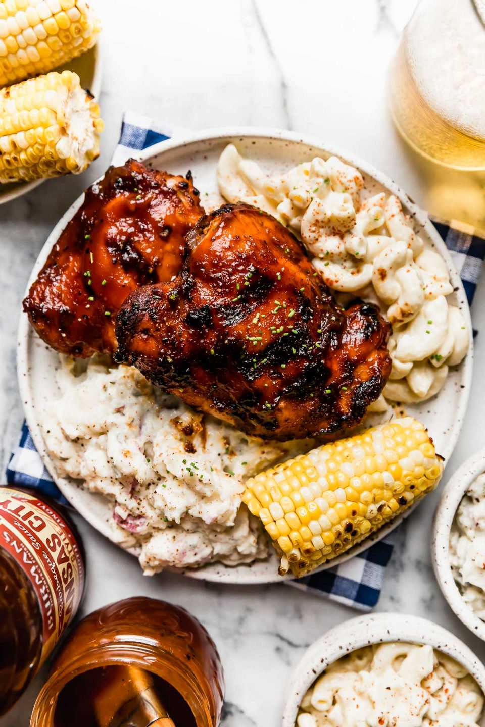 Grilled BBQ chicken on a plate with macaroni salad, potato salad, & corn on the cob. The plate is surrounded by more side dishes, extra BBQ sauce & a glass of beer.