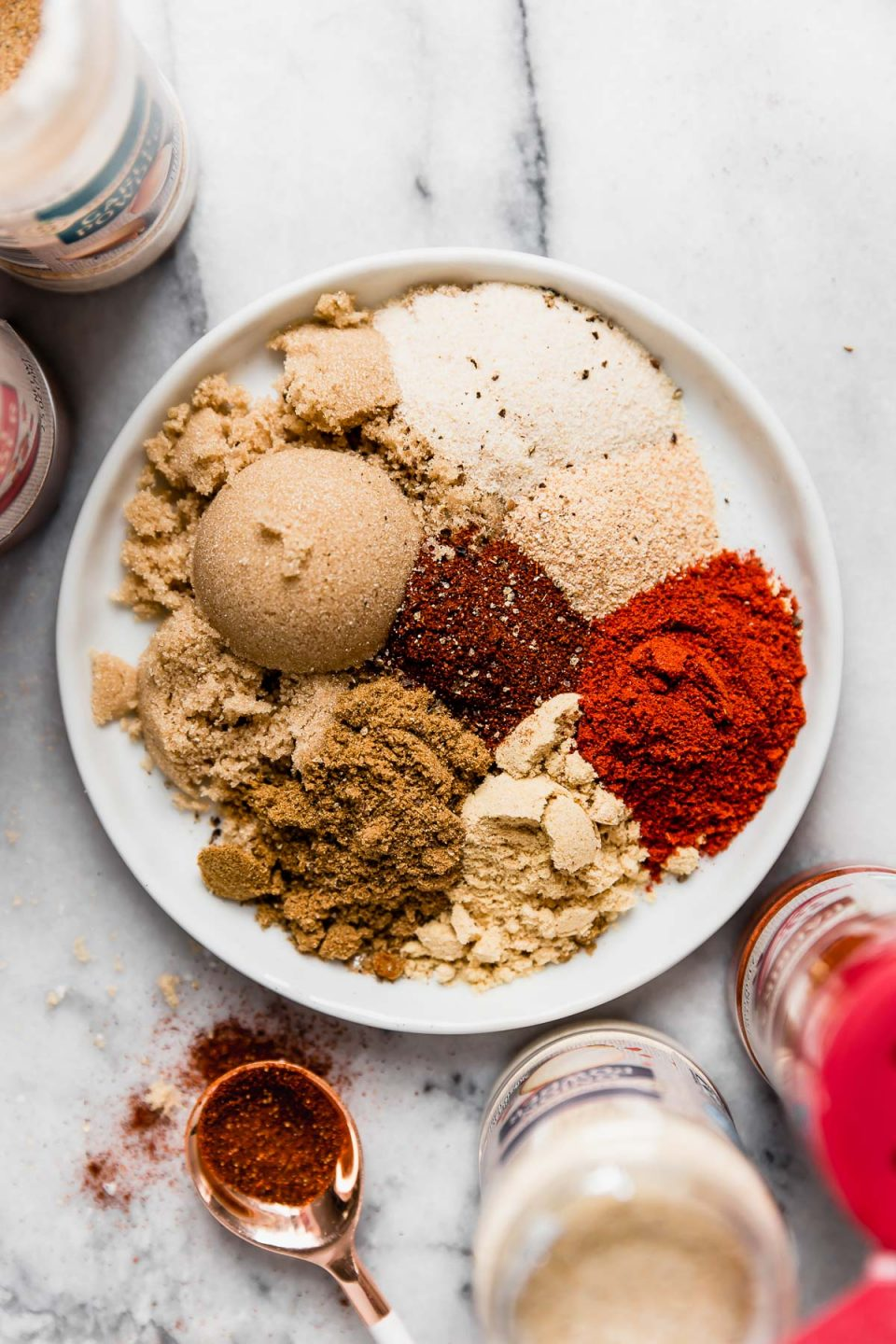 Ingredients for the BEST dry rub arranged on a small white plate, surrounded by bottles of spices & dried herbs from ALDI.