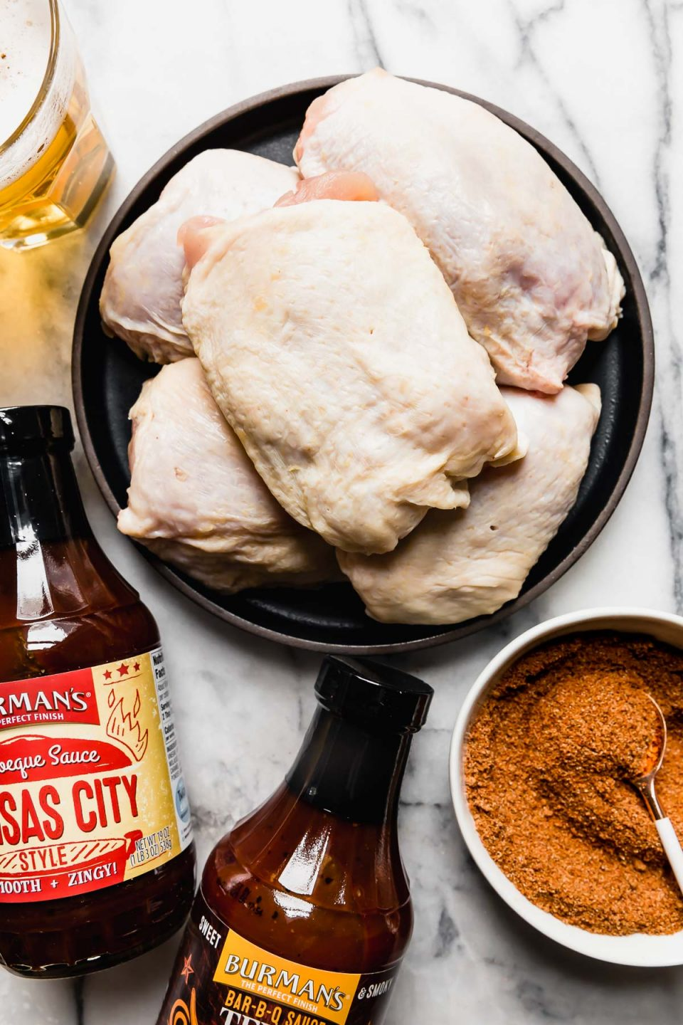 Ingredients for the easiest grilled BBQ chicken recipe! Chicken thighs, beer, BBQ sauce & a simple dry rub arranged on a white marble surface.