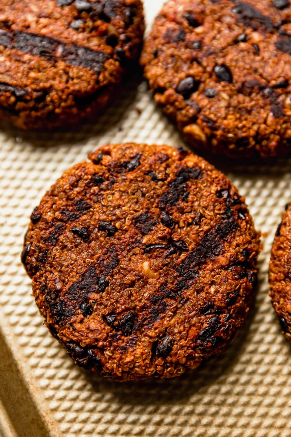Grilled black bean burgers on a small gold baking sheet.