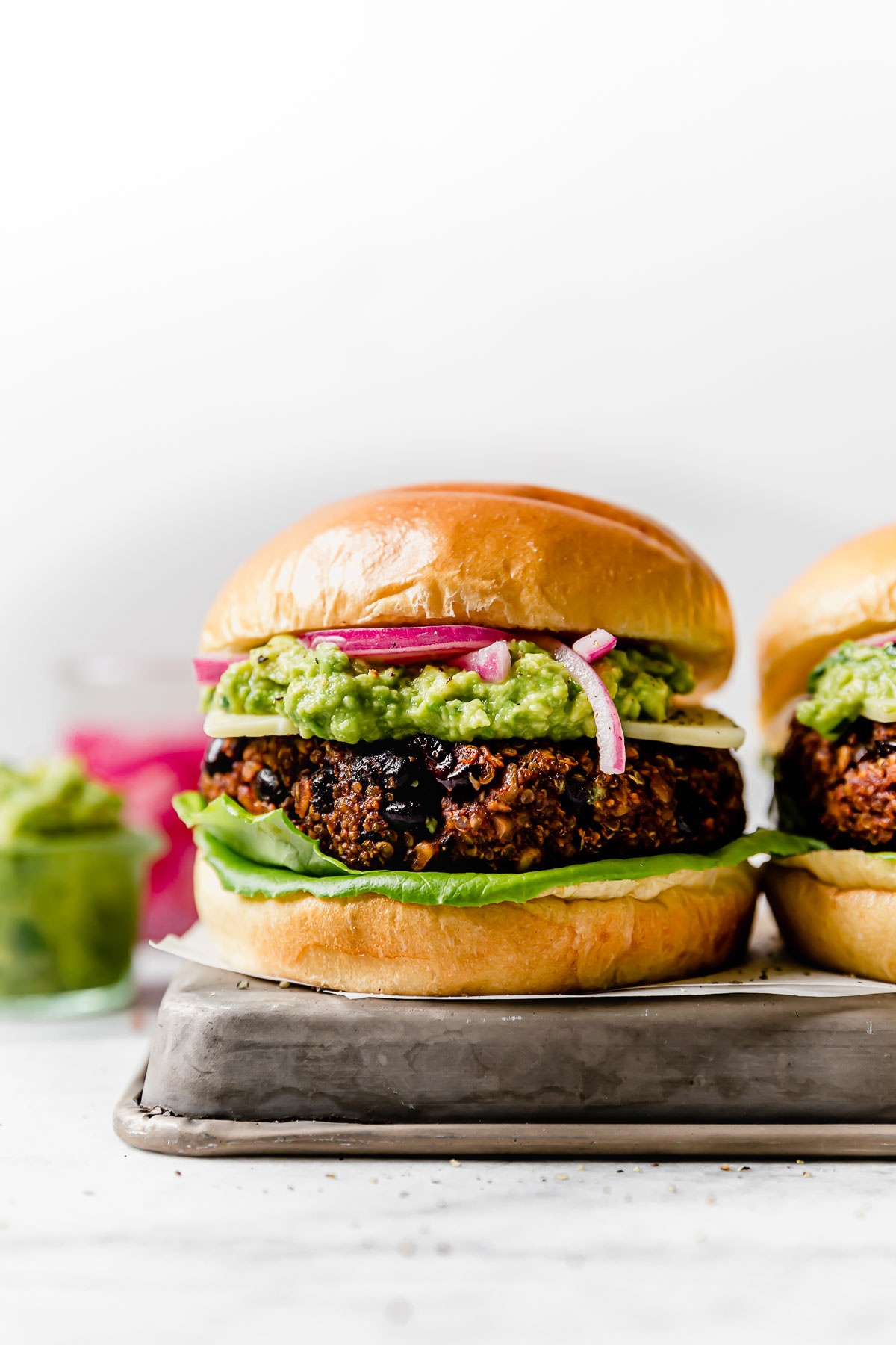 Grilled Black Bean Burgers on brioche buns, topped with lettuce, cheese, guacamole & pickled red onion. The burgers are placed on a small metal tray, with jars of guacamole & pickled red onions in the background.