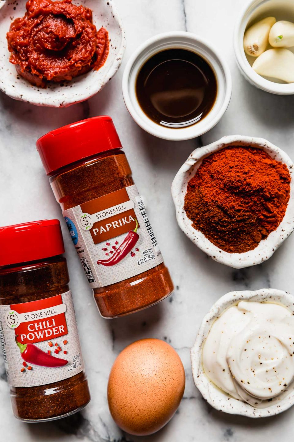 Meatless burger ingredients arranged on a white marble surface: tomato paste, spices, garlic, mayo, egg & Worcestershire sauce.