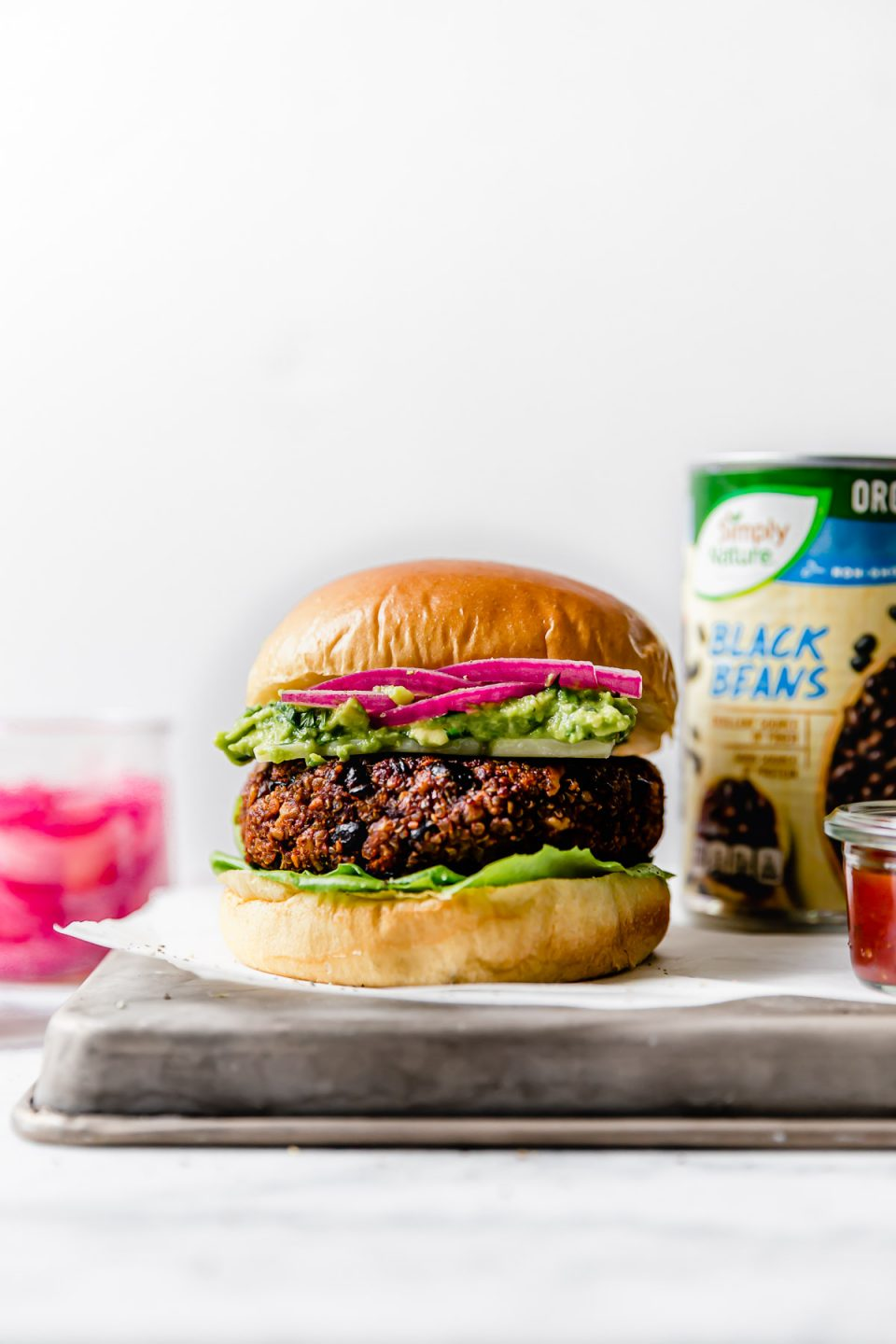 Grilled Black Bean Burgers on brioche buns, topped with lettuce, cheese, guacamole & pickled red onion. The burgers are placed on a small metal tray, with jars of guacamole & pickled red onions & a can of Simply Nature Organic Black Beans in the background.