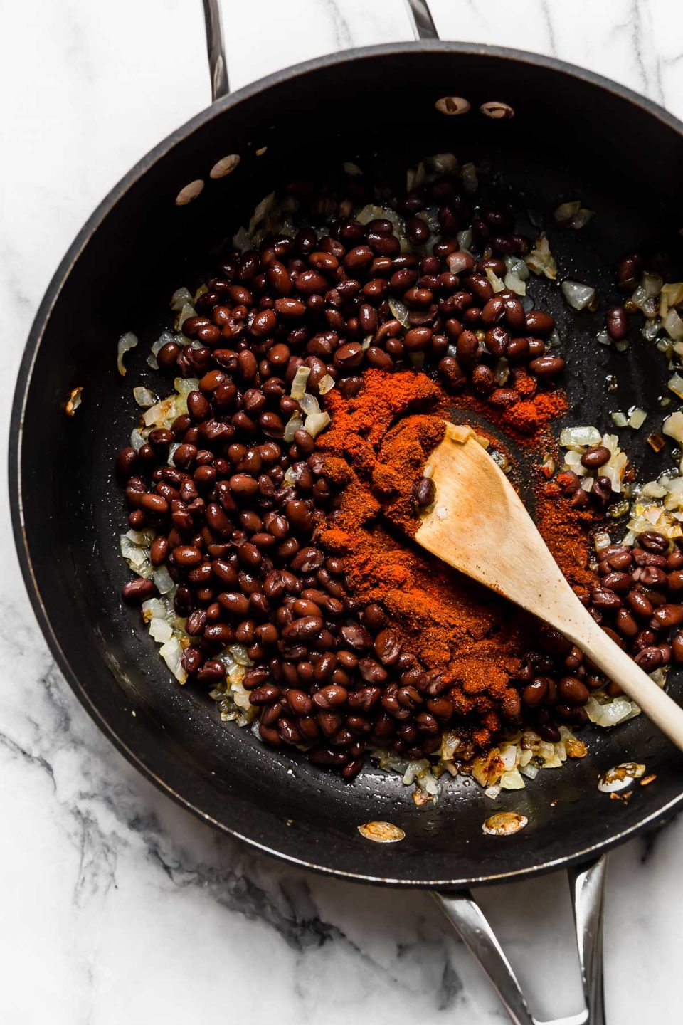 Toasting black beans with onions & spices for plant-based burger recipe.