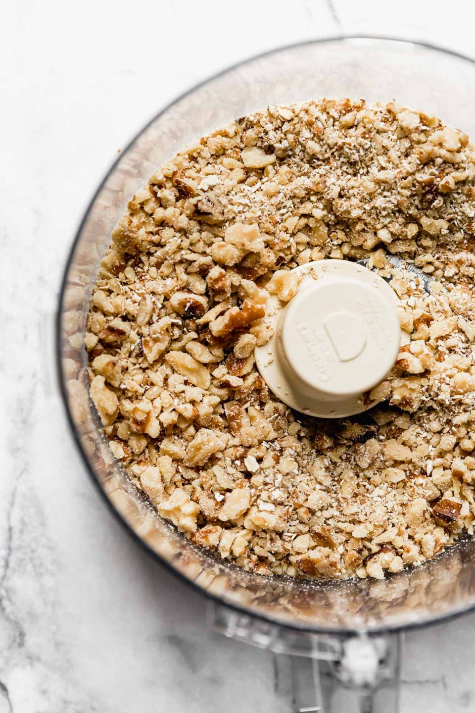 Crushing oats & walnuts in food processor for meatless burger recipe.