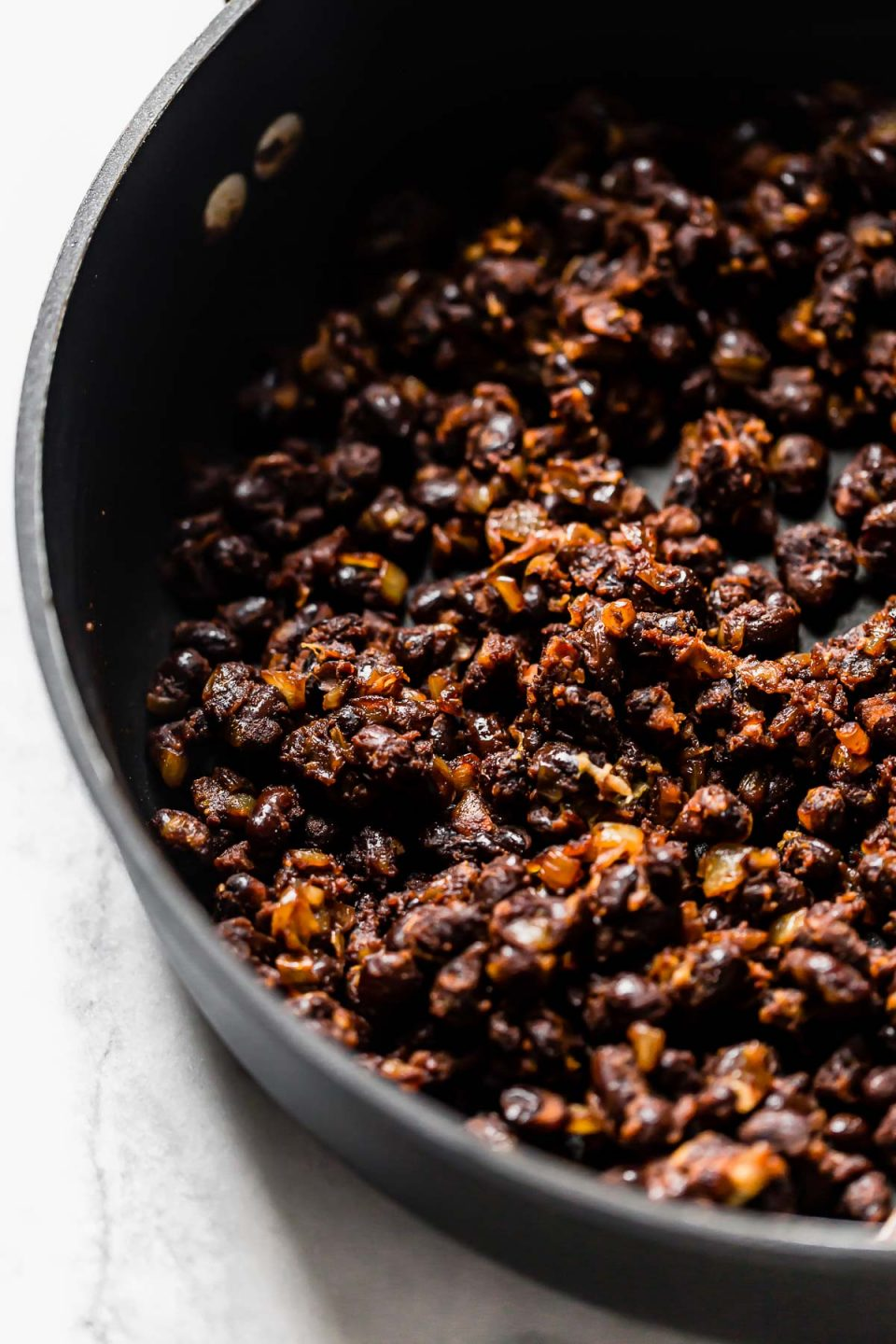 Close up photo of toasted black beans with onions & spices for plant-based burger recipe.