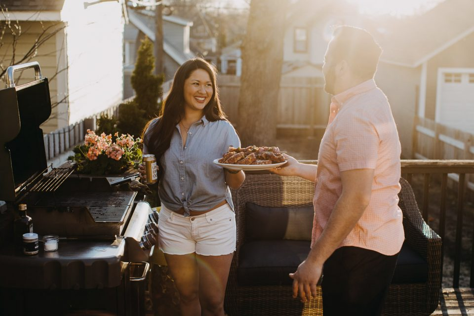 Jess of Plays Well with Butter handing a platter of food just grilled on her gas grill to her husband Chris.
