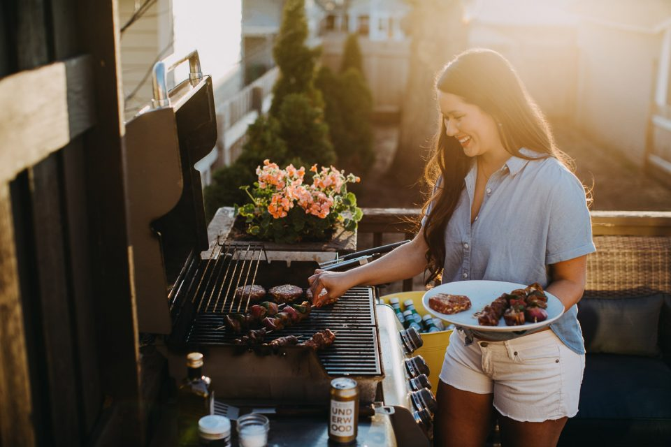 Jess of Plays Well with Butter takes a finished grilled kebab off of her gas grill.