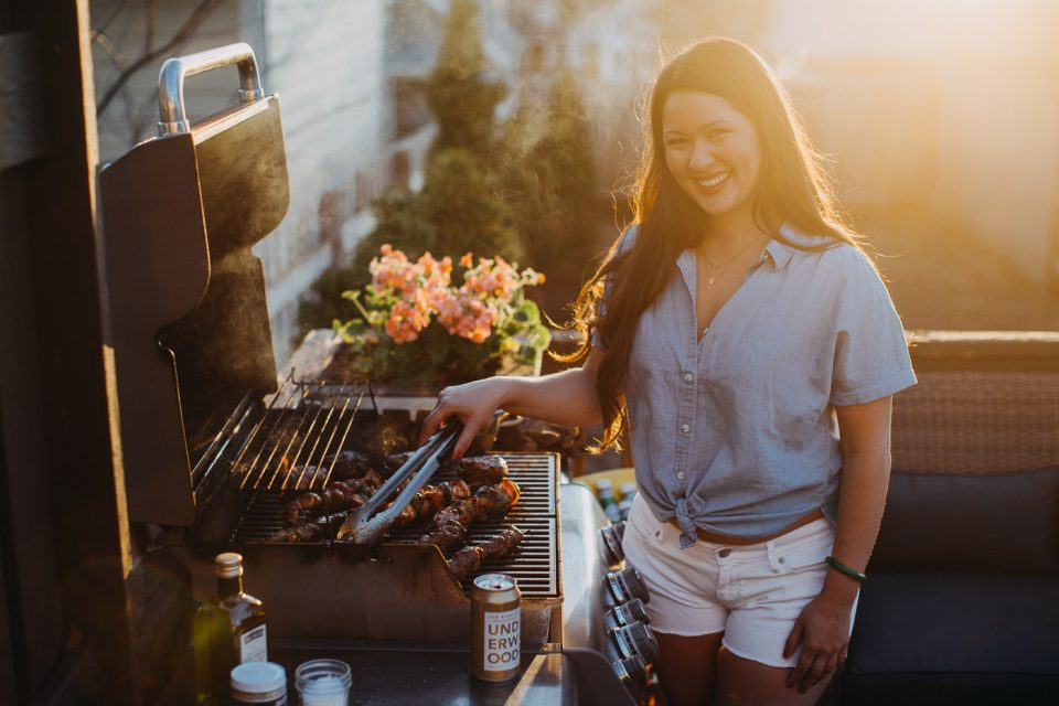 Jess of Plays Well with Butter using grill tongs while grilling kebabs on a gas grill