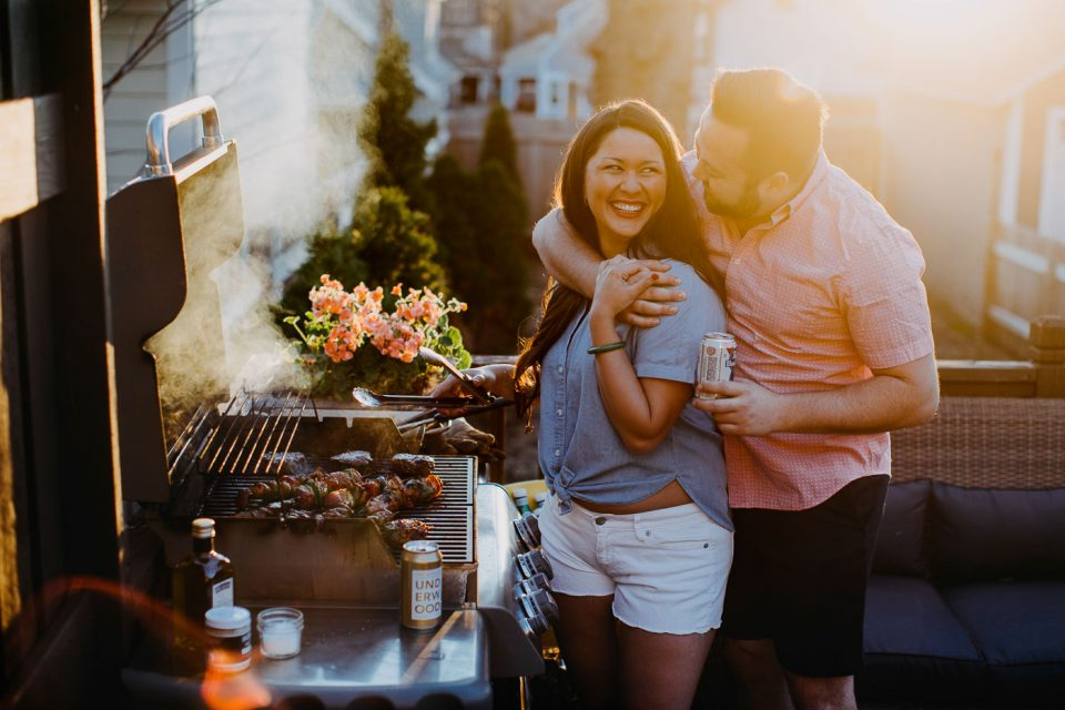 Jess of Plays Well with Butter grilling outside with grill tongs in hand while getting a hug from her husband Chris.