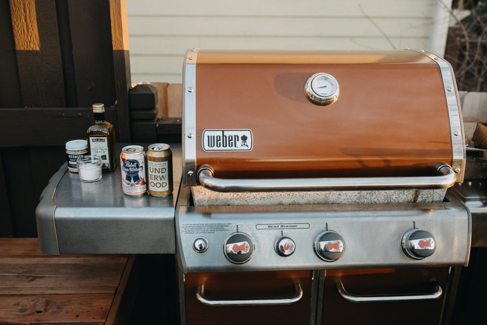 Weber Genesis II gas grill with lid closed sitting outside on a deck