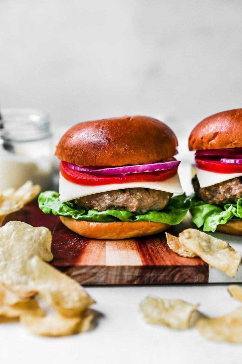 2 Turkey burgers sitting on a wooden board. The turkey burgers are topped with lettuce, cheese, tomato & red onion. The turkey burgers are on golden hamburger buns, surrounded by potato chips.