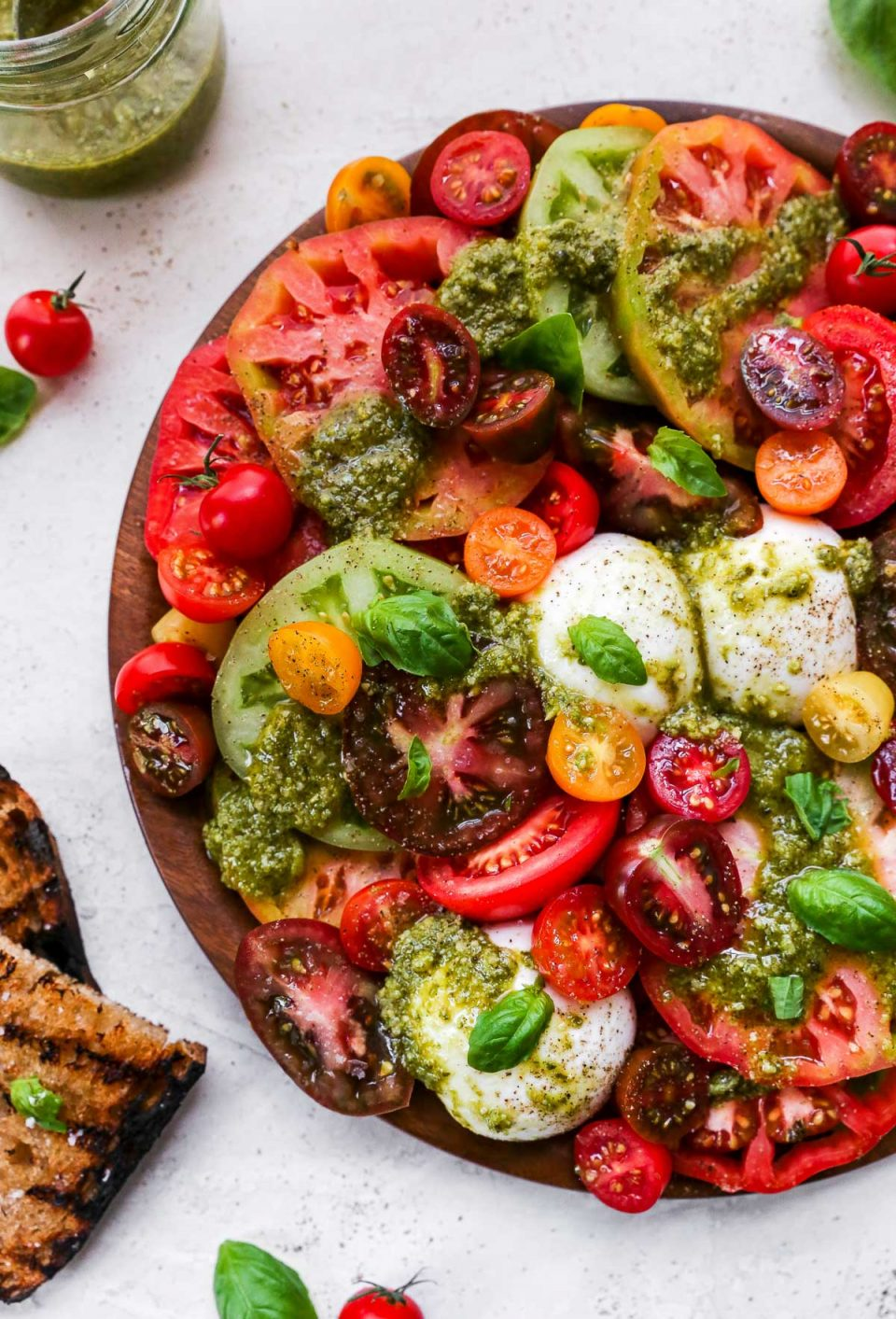 Heirloom tomato burrata salad arranged on a large wooden serving board, topped with vibrant green fresh pesto sauce. The board is surrounded by a few slices of grilled bread & a jar of basil pesto sauce.