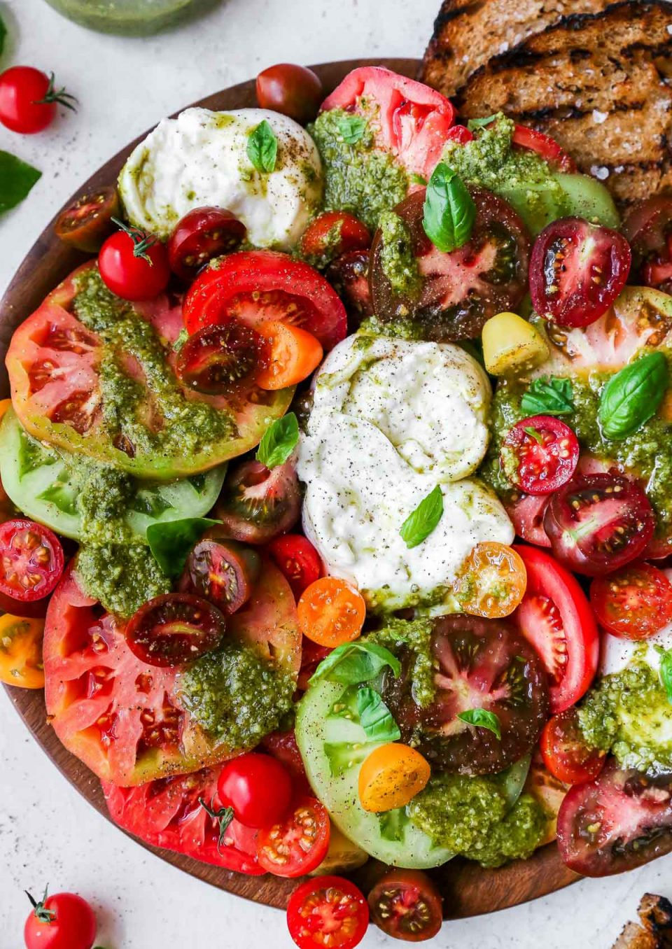 Heirloom tomato burrata salad arranged on a large wooden serving board, topped with vibrant green fresh pesto sauce. The board is surrounded by a few slices of grilled bread & some red cherry tomatoes.