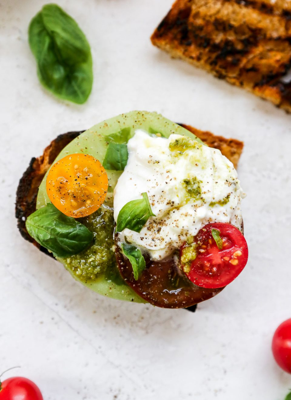 Burrata Caprese Salad served on a piece of grilled bread. The bread sits atop a neutral background, surrounded by whole cherry tomatoes, fresh bail leaves & a jar of basil pesto sauce.