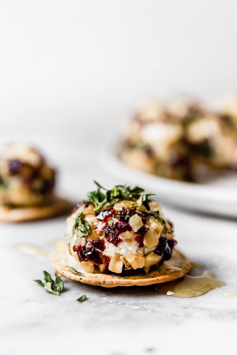 Goat cheese truffle, coated with chopped nuts, tart cherries, & fresh herbs, served on a cracker, topped with honey. There are more goat cheese balls in the background on a small white plate.