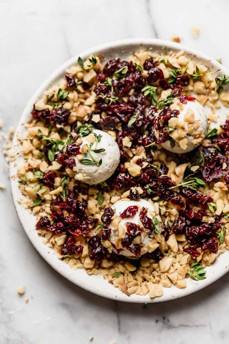 Rolling goat cheese balls in coating of chopped nuts & dried Montmorency tart cherries on a small white plate.