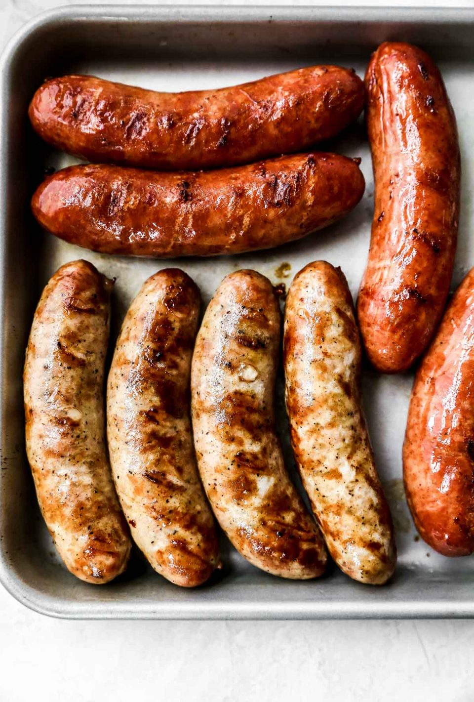 Grilled sausage links on a small baking sheet.