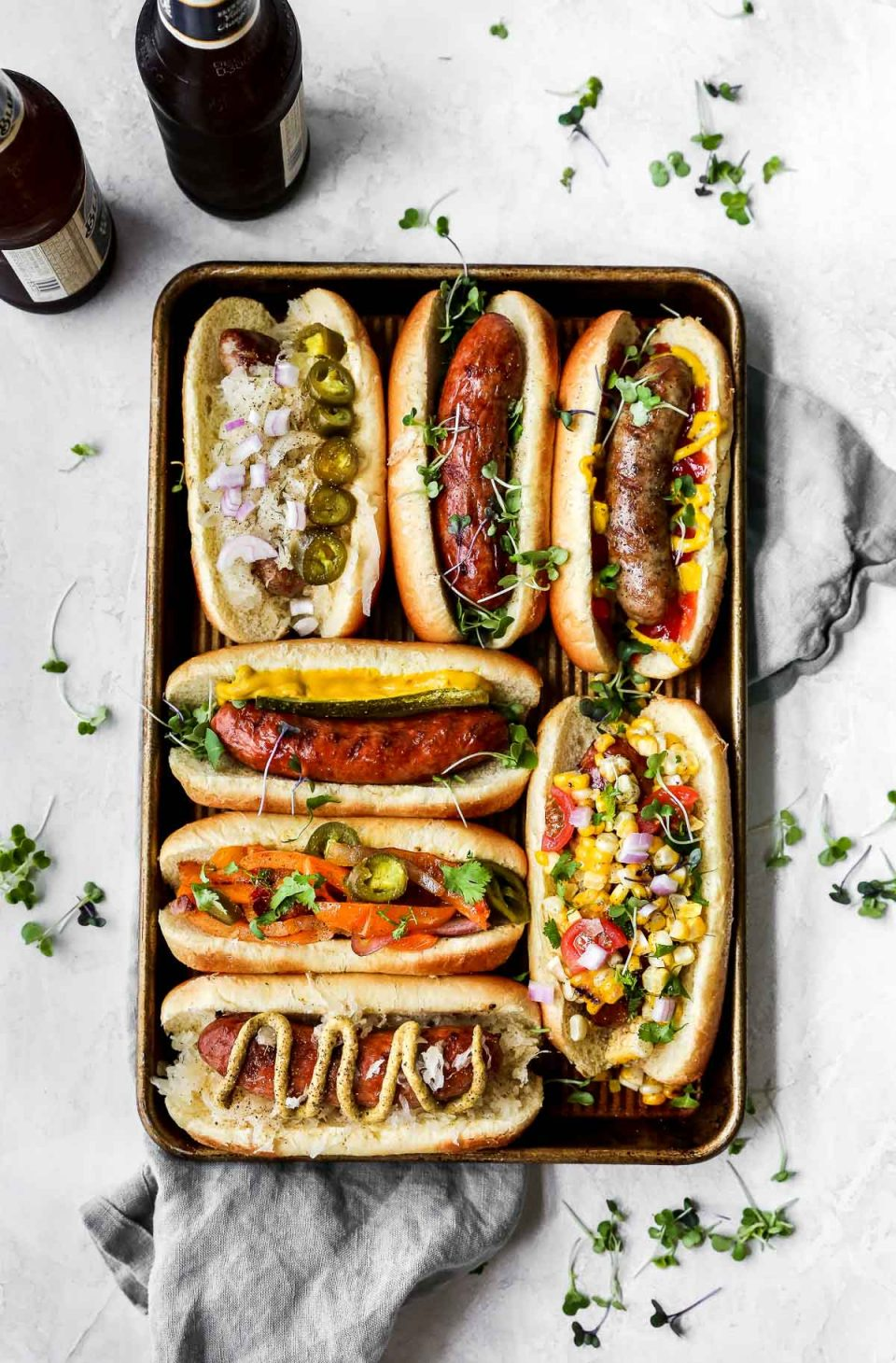 All kinds of grilled sausage on a small baking sheet! The sausages are served on buns with a variety of toppings (mustard, pickled veggies, etc.). The baking sheet is on a grey surface with a grey linen napkin, next to a few bottles of beer.