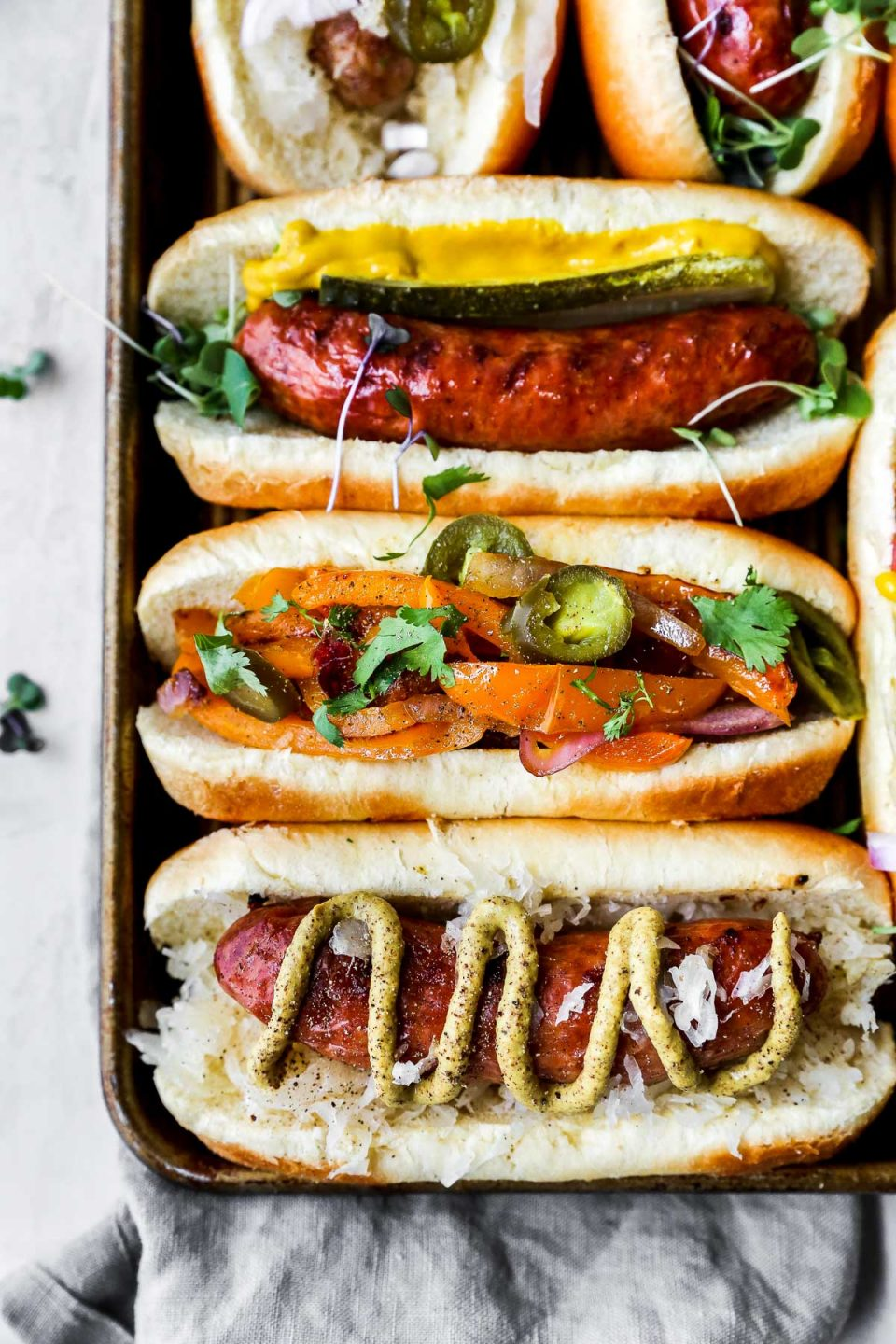 Grilled sausage on a small baking sheet. The sausages are served on buns with a variety of toppings (mustard, pickled veggies, etc.). The baking sheet is on a white surface with a grey linen napkin.