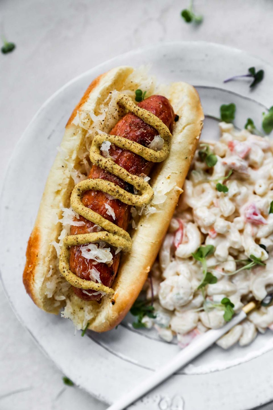 Close up of Grilled Sausage on a bun, topped with brown mustard. The sausage is plated with a simple macaroni salad on the side, on a white plate with a gold & white fork.