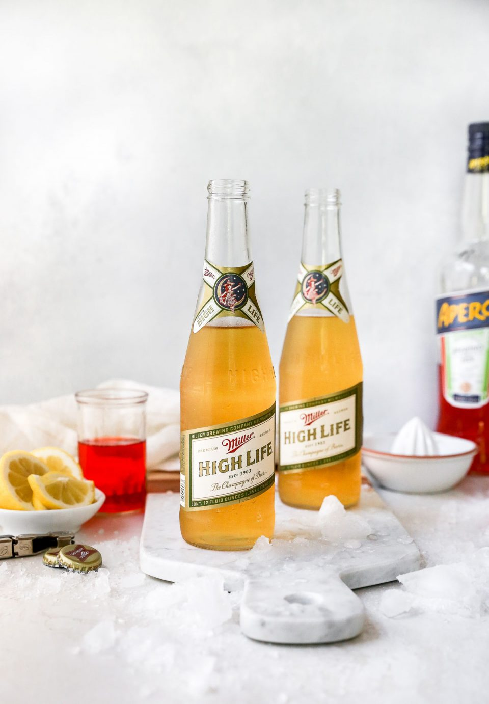 Spaghett drink ingredients: Miller High Life, lemons & Aperol liquor grouped close together on a white surface.