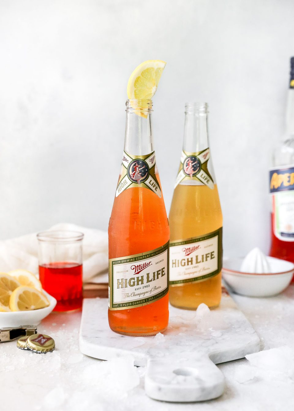 2 Spaghett Cocktails served in Miller High Life bottles. The beer bottles are on a white surface, surrounded by lemon wedges, ice & some Aperol liquor.