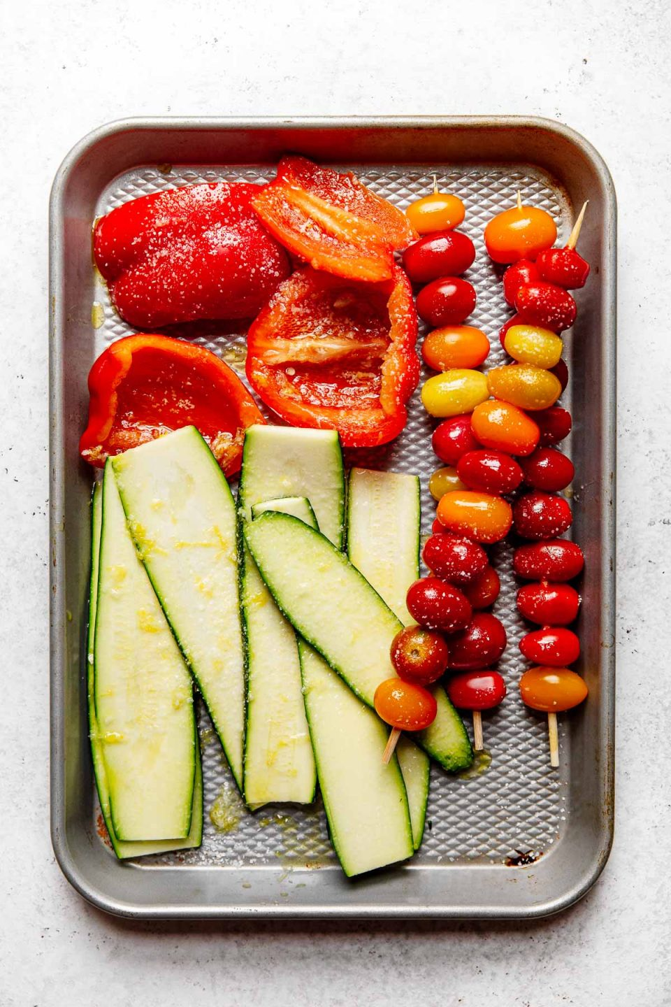 Marinated veggies (Zucchini, bell pepper, tomatoes) on a quarter baking sheet atop a white surface.