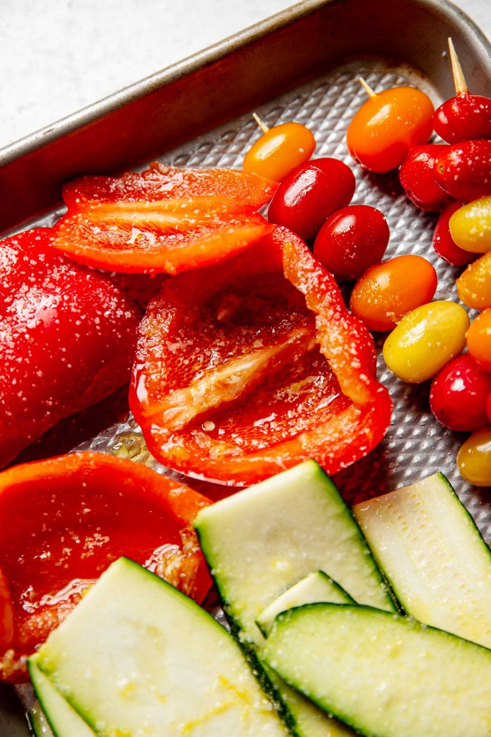 Close up of marinated bell pepper on a quarter baking sheet, ready to be grilled.