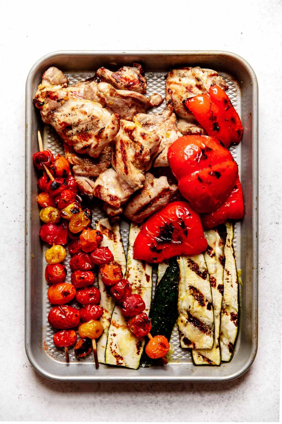 Grilled Chicken & Veggies (Zucchini, bell pepper, tomatoes) on a quarter baking sheet atop a white surface.