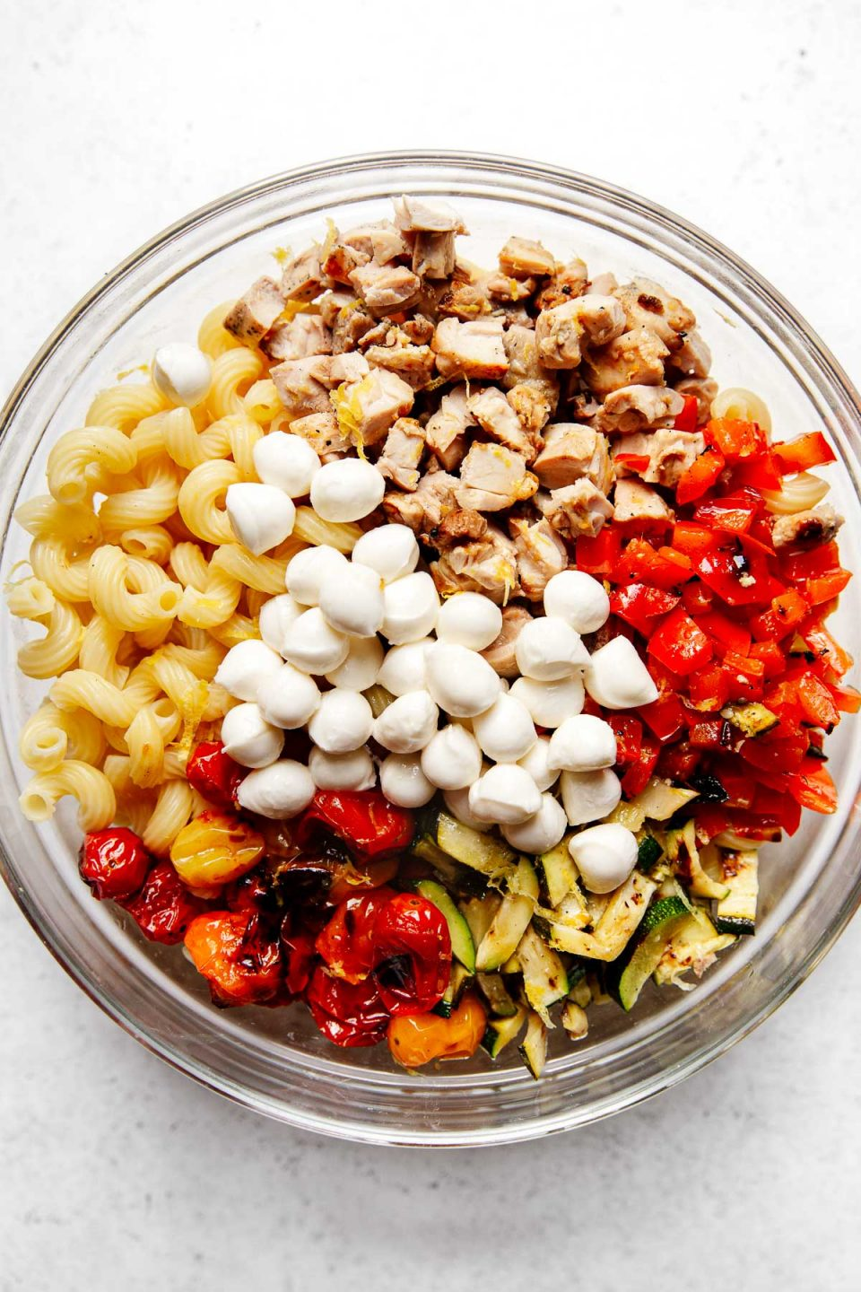 Summer pesto pasta salad ingredients arranged in groups in a large mixing bowl: cavatappi pasta, diced grilled chicken, diced grilled vegetables (bell pepper, zucchini & tomatoes), fresh mozzarella pearls.