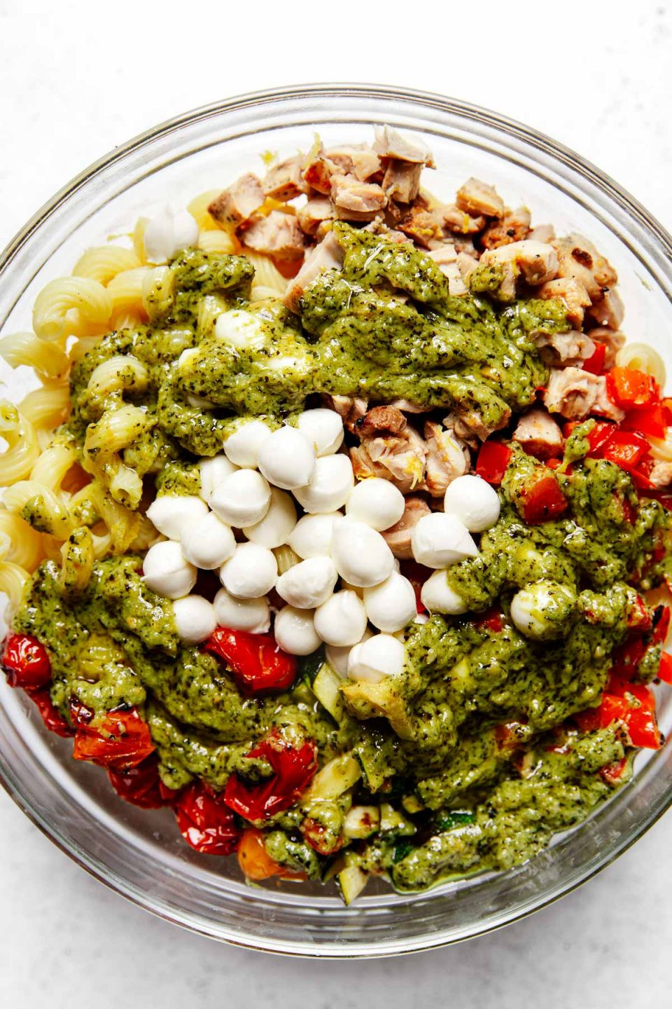 Summer pesto pasta salad ingredients arranged in groups in a large mixing bowl: cavatappi pasta, diced grilled chicken, diced grilled vegetables (bell pepper, zucchini & tomatoes), fresh mozzarella pearls, topped with bright green pesto sauce.