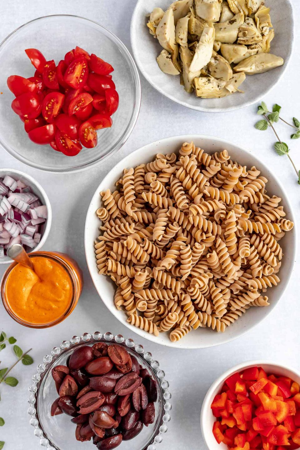 Vegan Italian pasta salad ingredients arranged on a light blue surface in individual bowls: artichoke hearts, diced bell pepper, diced red onion, fusilli pasta, kalamata olives, & halved cherry tomatoes.