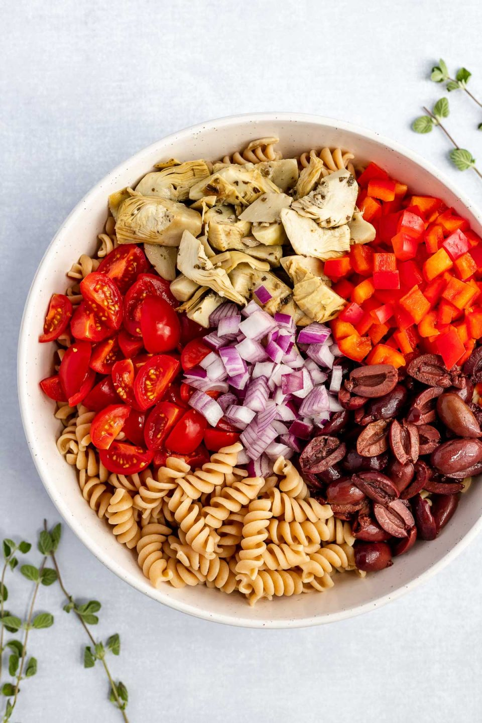 Vegan Italian pasta salad ingredients grouped in a large mixing bowl: pasta, artichoke hearts, red bell pepper, kalamata olives, tomatoes, & red onions. The bowl sits atop a white blue surface, with some fresh oregano leaves scattered around it.