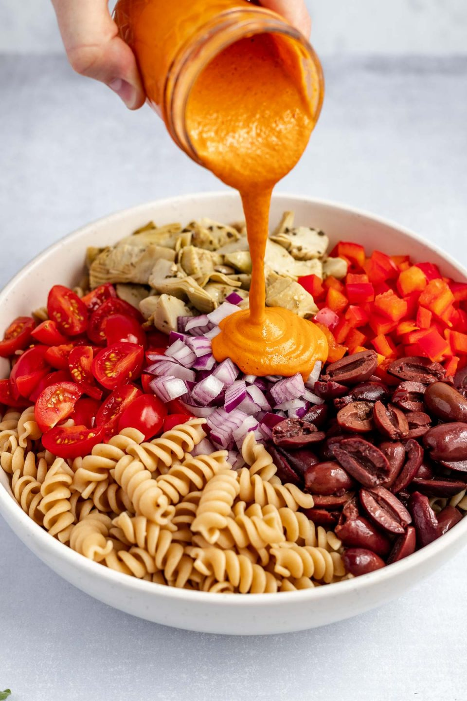 A woman's hand pours roasted red pepper cashew dressing out of a small glass jar, into a large mixing bowl with the rest of the easy Italian pasta salad ingredients. The bowl sits atop a light blue surface.