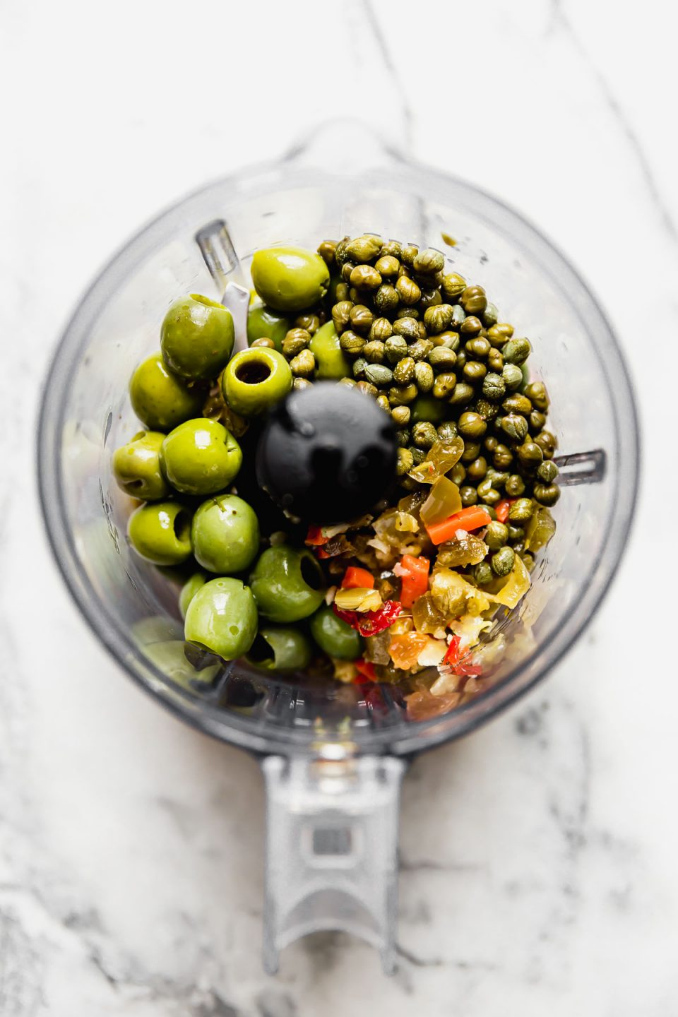 Castelvetrano-giardiniera relish ingredients (castelvetrano olives, giardiniera, & capers) in the bowl of a small food processor, placed atop a white marble surface.
