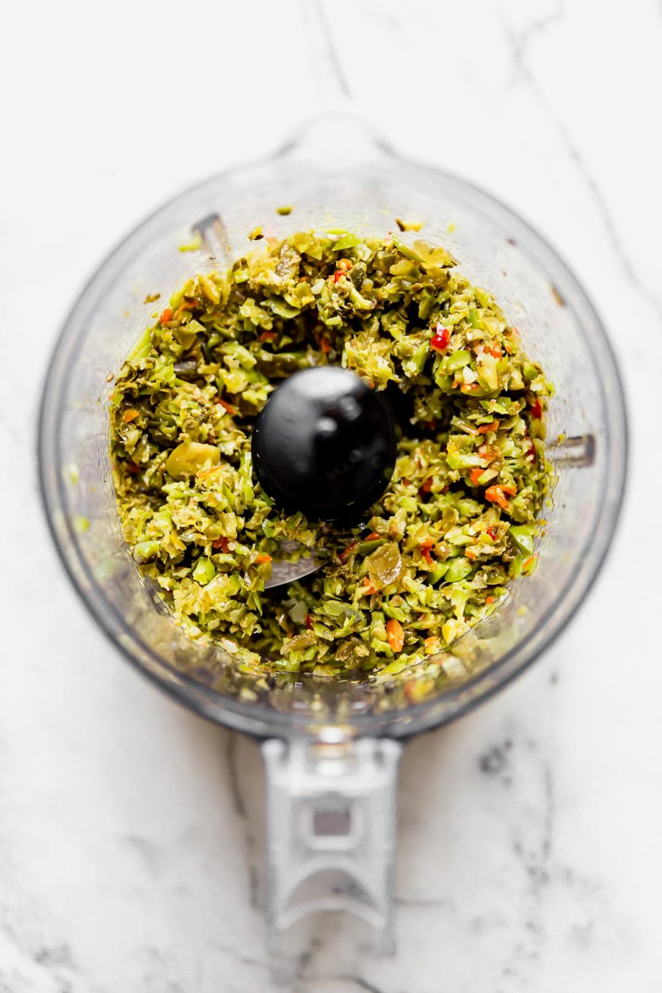 Finely chopped castelvetrano-giardiniera relish in the bowl of a small food processor, placed atop a white marble surface.