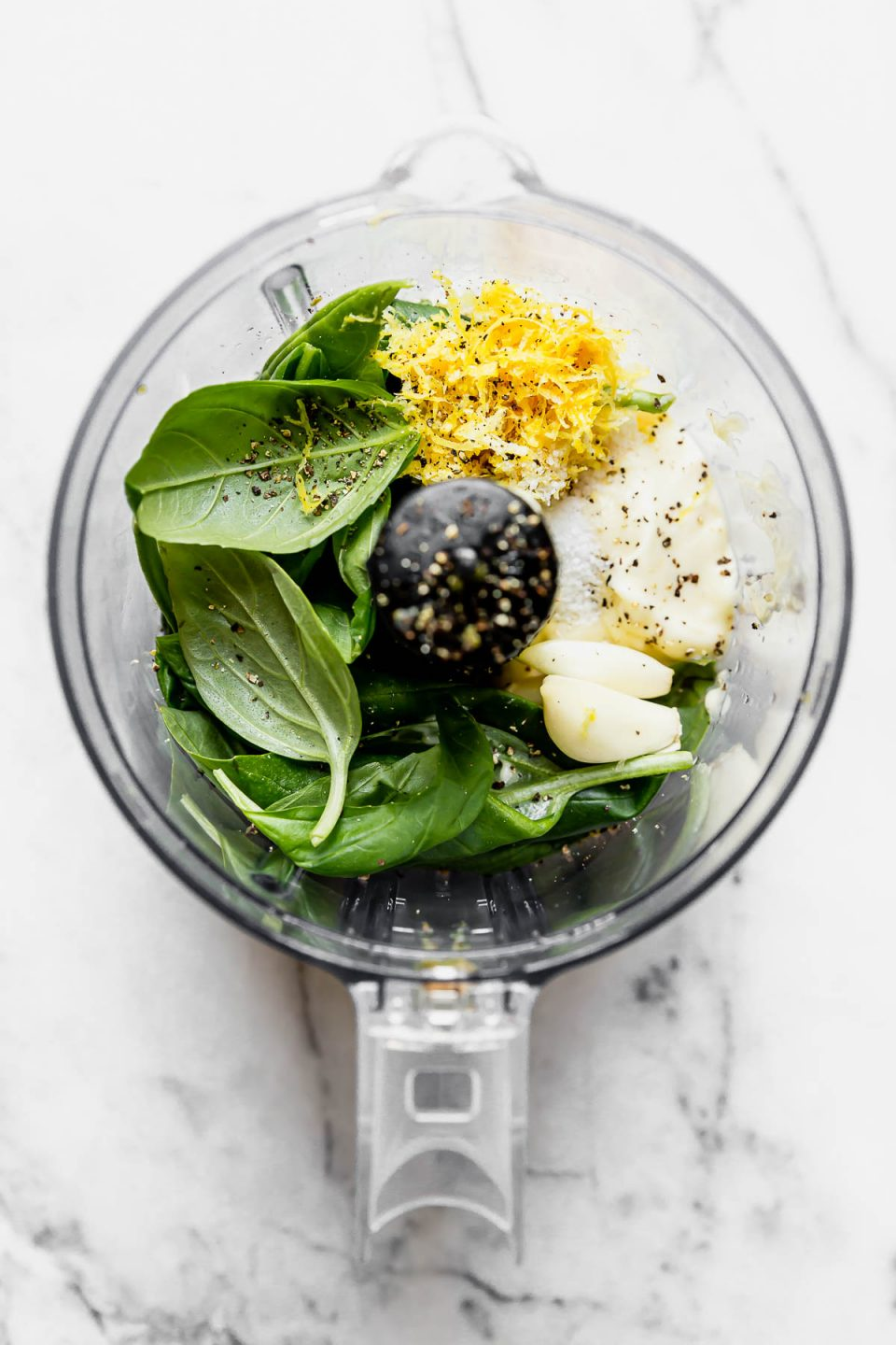 Lemon basil aioli ingredients (basil, mayonnaise, garlic cloves, & lemon zest) placed in the bowl of a small food processor, atop a white marble surface.