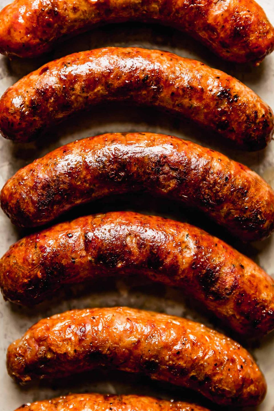 Close up photo of 6 grilled Italian sausages.
