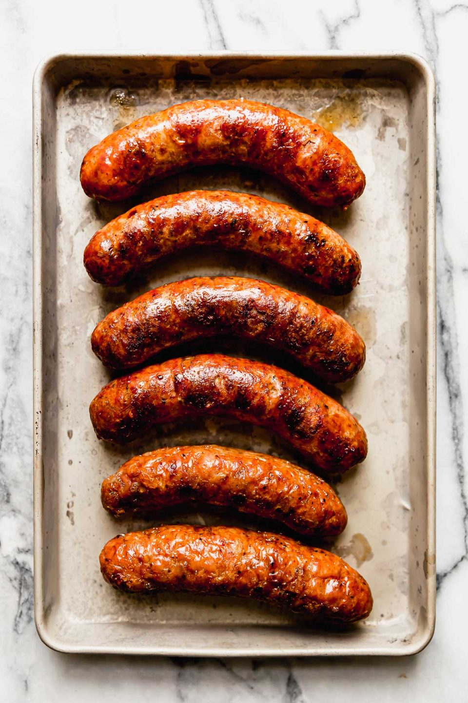 6 grilled Italian sausages shown on a small baking sheet atop a white marble surface.